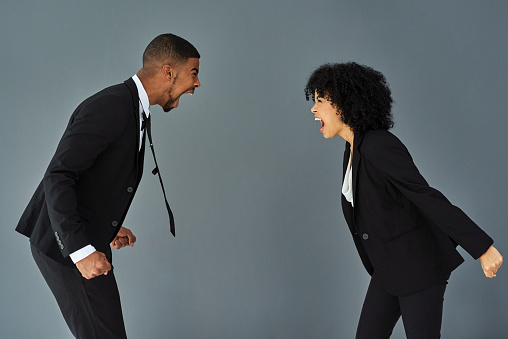 Studio shot of a young businessman and businesswoman yelling at each other against a grey background