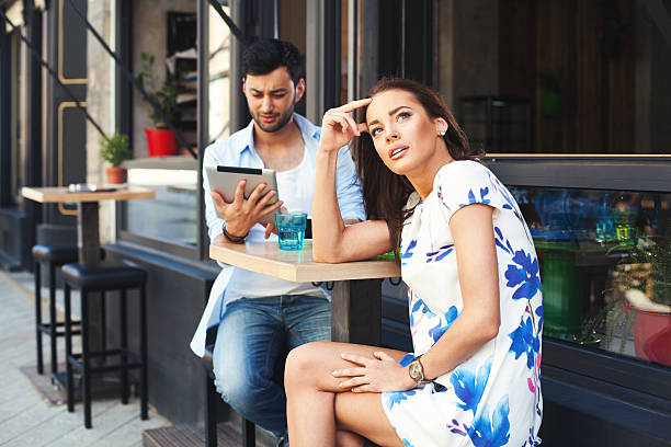 Bad date Bad date.  Man having fun with digital tablet during a date with a beautiful woman. bad date stock pictures, royalty-free photos & images