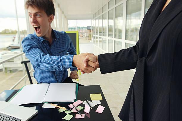Bad deal. Woman and man shake hands. Partnership. stock photo