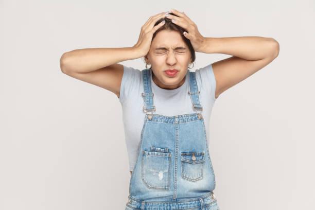 schlechtes konzept, emotionen und gefühle. kopfschmerzen. zigeunerin berühren den kopf und haben eine migräne. - jeans overall stock-fotos und bilder