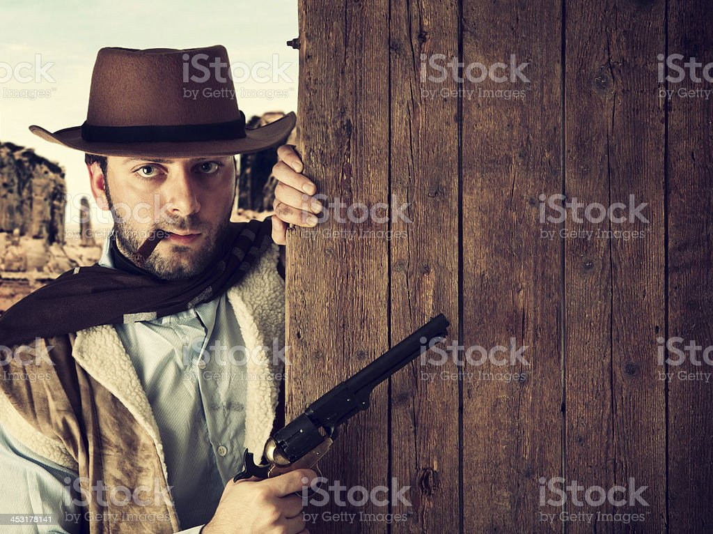 Bad gunman indicates with the gun a wooden plank stock photo