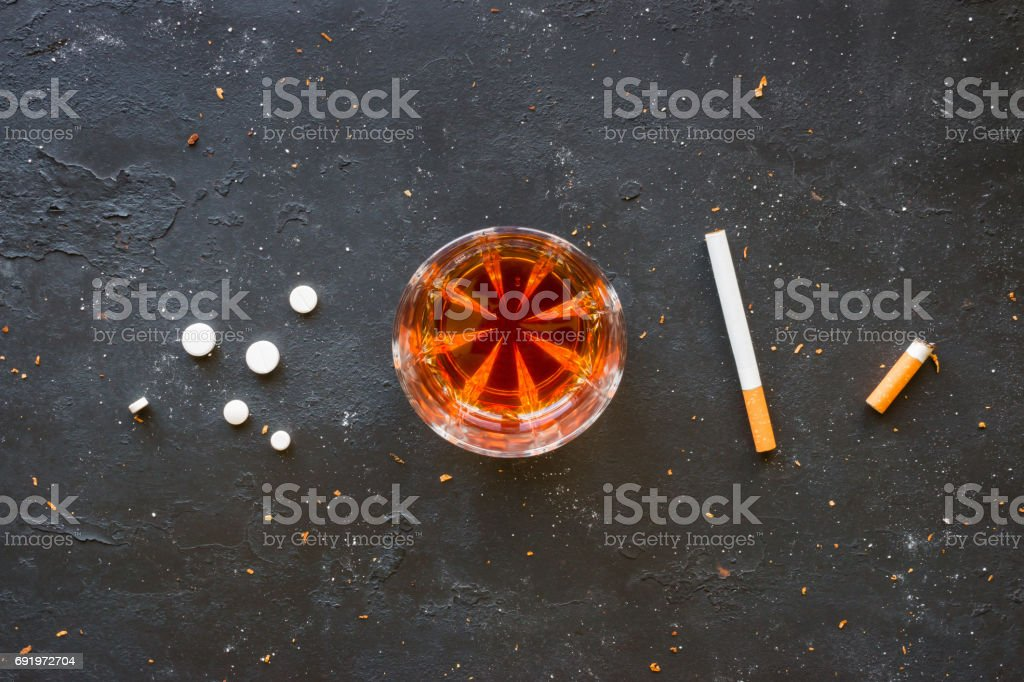 Bad habits in a row on a black background - drugs, alcohol, smoking stock photo