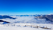 View on fog-covered valley in Bad Kleinkirchheim, Austria. Big ski resort. The slopes are perfectly gravelled. There is a protection fence along the edge. Lots of snow caped mountains. Winter in Alps