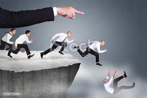 Bad direction in business concept. Big leader hand giving wrong direction causine his workers falling down at the edge of a cliff
