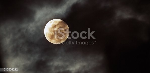The full moon seen against a pitch black sky with drifting misty clouds. Beautiful, romantic,  and just a little bit spooky.
