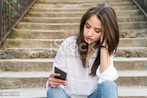 А sad girl is sitting on stairs and looking at her phone
