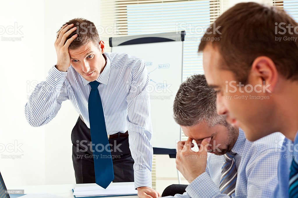 Bad news Three worried businessmen solving a problem during business meeting in a board room. 30-34 Years Stock Photo