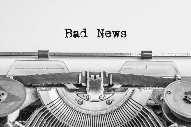 Bad News typing text vintage typewriter Bad News typing text vintage typewriter with black ink heading on aged paper front page stock pictures, royalty-free photos & images