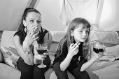 """""""Mother or childminder sitting on couch with a little girl, both of them smoking and drinking a glass of wine while watching an offscreen TVMore like this"""""""