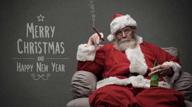 bad santa celebrating at home - cartolina di natale foto e immagini stock