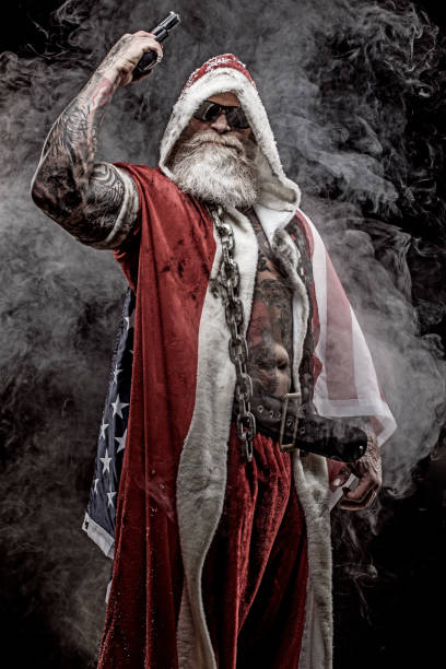 Bad Santa Claus Portrait of bad ass, weapon wielding tattooed bad Santa Claus with the american star spangled banner american flag tattoos for men stock pictures, royalty-free photos & images