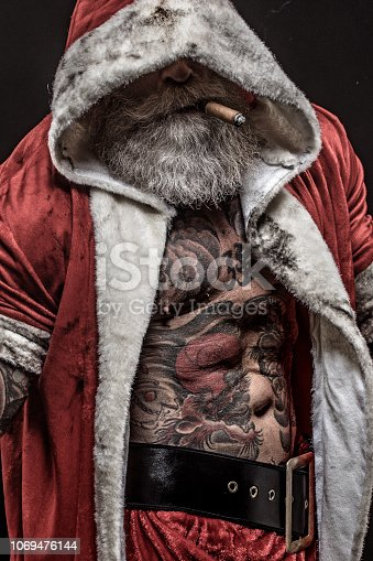 Portrait of weapon wielding tattooed bad ass Santa Claus