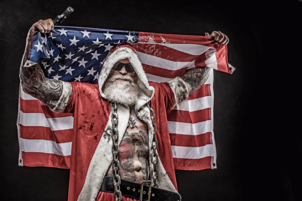 Bad Santa Claus with gun and american flag Portrait of weapon wielding tattooed bad ass Santa Claus with American Flag american flag tattoos for men stock pictures, royalty-free photos & images