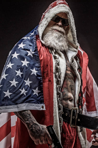 Bad Santa Claus with gun and American Flag Portrait of weapon wielding tattooed bad ass Santa Claus draped in the stars and stripes american flag tattoos for men stock pictures, royalty-free photos & images