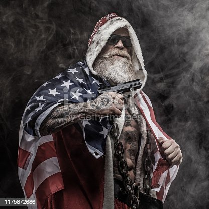 Portrait of weapon wielding tattooed bad ass Santa Claus draped in the stars and stripes