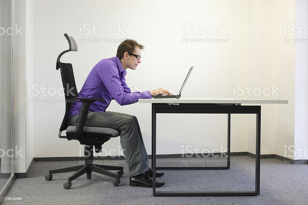 bad sitting posture at laptop stock photo