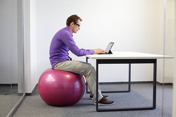 bad sitting posture at tablet on stability ball bad sitting posture at tablet - business man on stability ball in his office bad posture stock pictures, royalty-free photos & images