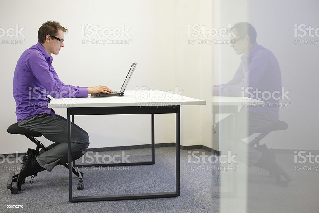 bad sitting posture at workstation. man on kneeling chair stock photo