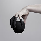 Studio shot of a woman's hand holding a black apple