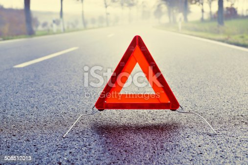istock Bad Weather Driving - Warning Triangle on a Misty Road 508512013