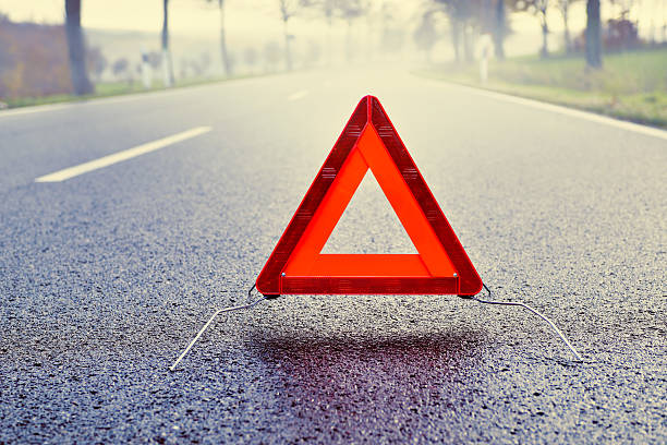 bad weather driving - warning triangle on a misty road - triangle shape stock photos and pictures