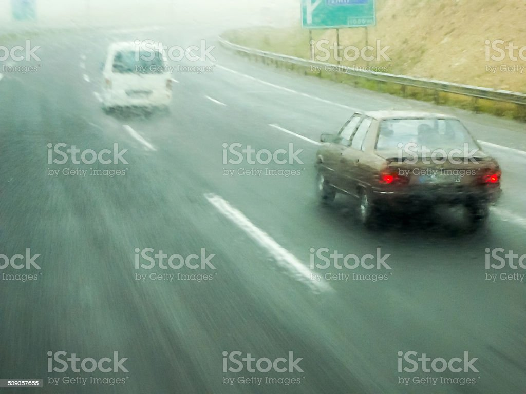 Bad weather on the highway - overtaking minibus and automobile. Water...