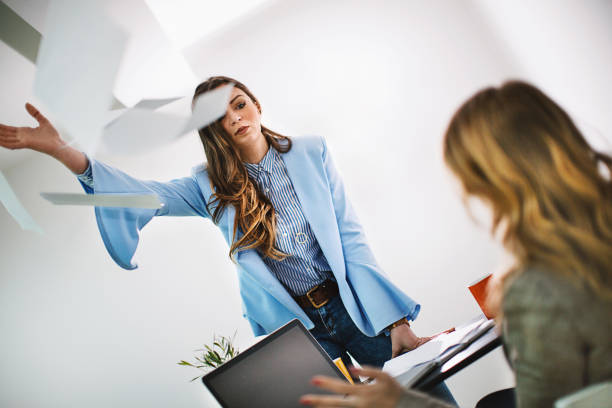Bad work environment. Superior businesswoman throwing paperwork at employee. Over the shoulder view. Horizontal. Tilted. agitation stock pictures, royalty-free photos & images