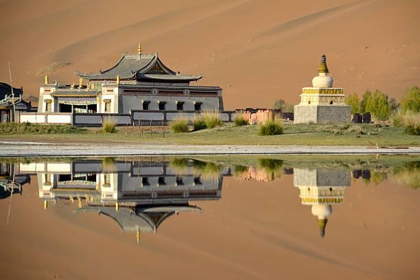 Badain Jaran Temple, reflecting on its lake, Inner Mongolia stock photo