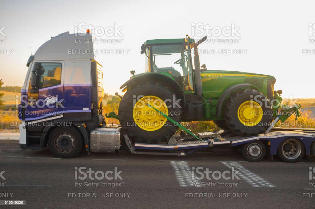 Badajoz, Spain - August 6th, 2017: Auto-transport trailer carrying the Row Crop Tractor John Deere 8320 stock photo