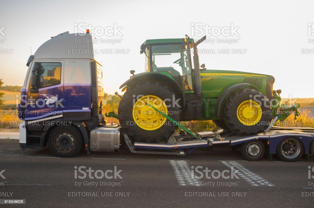 Badajoz, Spanien - 6. August 2017: Auto-Transport-Anhänger tragen die Row Crop Traktor John Deere 8320 – Foto