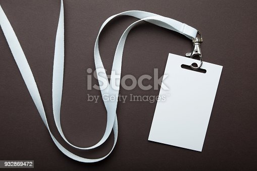 Empty businessman name card on a lanyard. Identification tag isolated on brown background. Mockup.