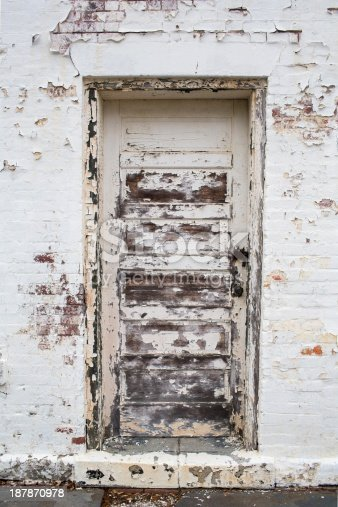 Old weathered and worn white painted exterior wall with a wooden door. Most of the wood on the door is exposed and you can see red bricks from the neglected building. The paint is old, worn and peeling, the neglected wall makes for a great grungy grunge Background Texture Pattern, or Graphic Element Wallpaper for poster design.