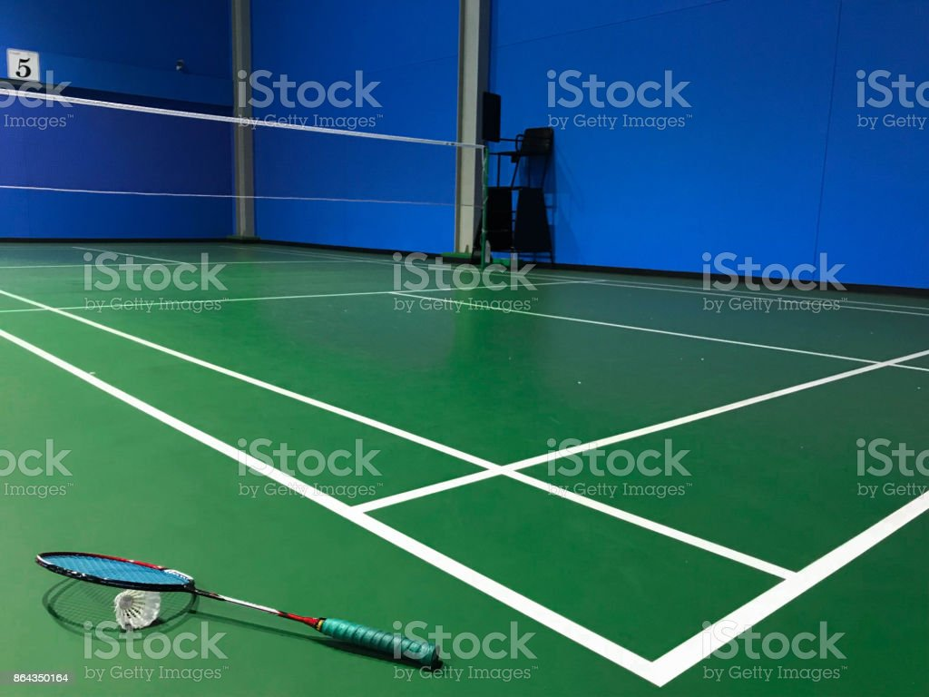 Badminton ball and racket on court floor with blue wall.