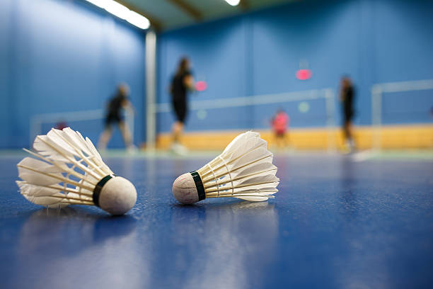 badminton courts with players competing; shuttlecocks in the foreground badminton courts with players competing; shuttlecocks in the foreground (shallow DOF; color toned image) badminton stock pictures, royalty-free photos & images