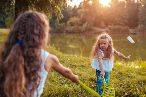Badminton. Little girl playing badminton with sister in spring park. Kids having fun outdoors. Outdoor games stock photo