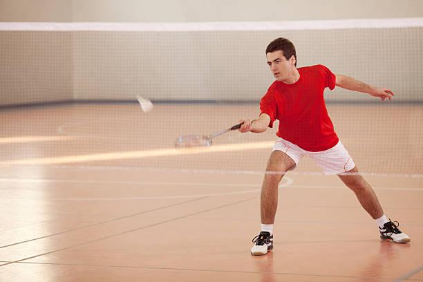 Jogador de Badminton com uma raquete na sua mão Pressione Peteca de Badminton - foto de acervo
