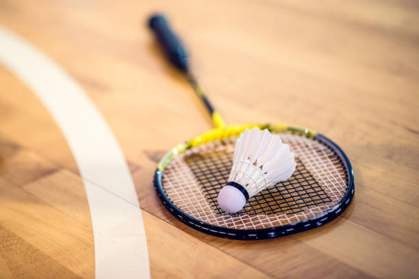Badminton racket and shuttlecock on the floor Close-up shot of a badminton racket and a shuttlecock on a wooden court flooring. badminton stock pictures, royalty-free photos & images