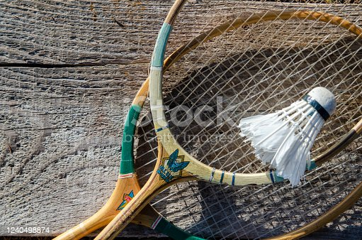 Badminton racket with shuttlecock ball on wood plank outdoors. Distance team recreation sport for healthy active life. Flat lay close up