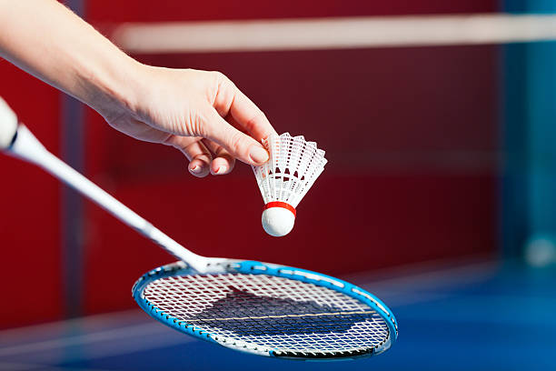 Badminton sport in gym - hand with shuttlecock Woman playing Badminton and doing sport in gym, only serve to be seen badminton stock pictures, royalty-free photos & images