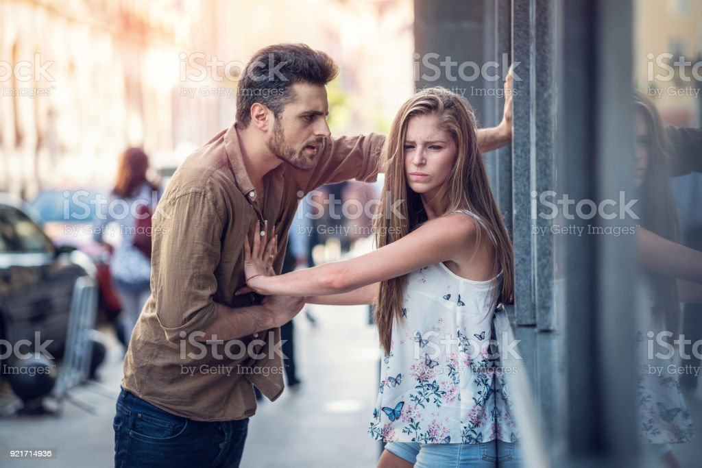 Bad-tempered man talking to his girlfriend on the street stock photo