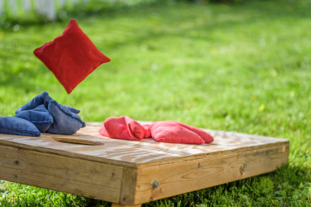 Bag flying onto corn hole board in backyard Homemade corn hole board game in grass in summertime leisure games stock pictures, royalty-free photos & images
