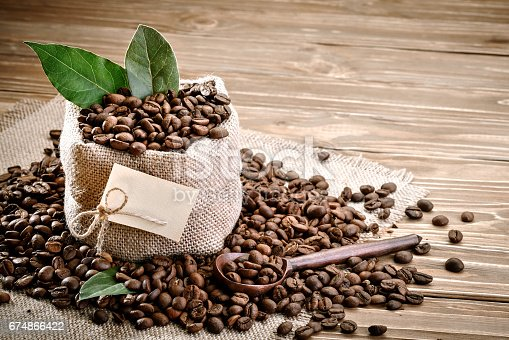 istock Bag of burlap filled with coffee beans on wooden background 674866422