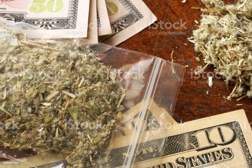 Bag of marijuana or weed on dollars. Drug trading concept. stock photo