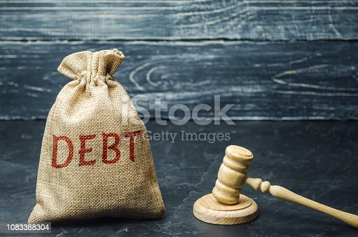 612372074 istock photo A bag of money and the word Debt and the hammer of the judge. Payment of taxes and of debt to the state. Concept of financial crisis and problems. Risk management. Debt exemption. Credit and loan 1083388304