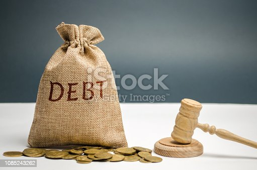 612372074 istock photo A bag of money and the word Debt and the hammer of the judge. Payment of taxes and of debt to the state. Concept of financial crisis and problems. Risk management. Debt exemption. Credit and loan 1085243262