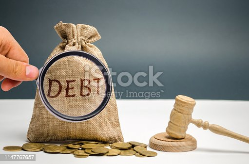 612372074 istock photo A bag of money and the word Debt and the hammer of the judge. Payment of taxes and of debt to the state. Concept of financial crisis and problems. Risk management. Debt exemption. Credit and loan 1147767657