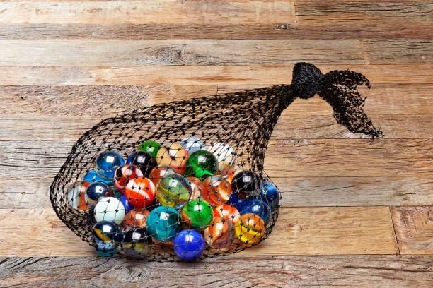 Tasche aus bunten Murmeln auf Holztisch – Foto