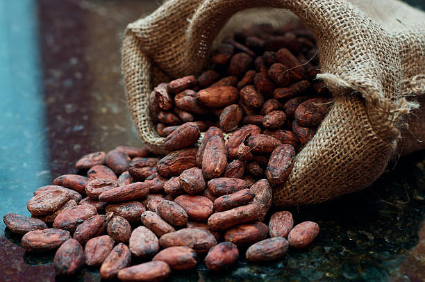 A bag of split cocoa beans on a granite countertop stock photo