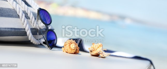istock bag on the beach with sunglasses, shells and towel 653747706