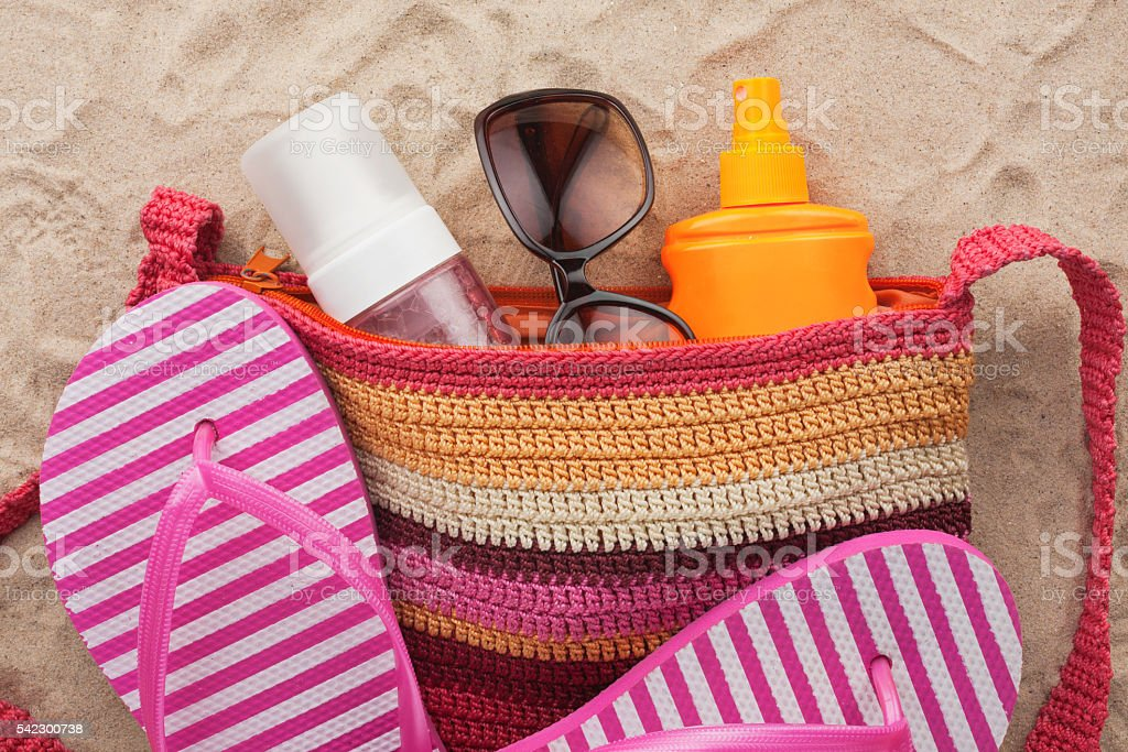 Bag with beach accessories lying on the sand stock photo